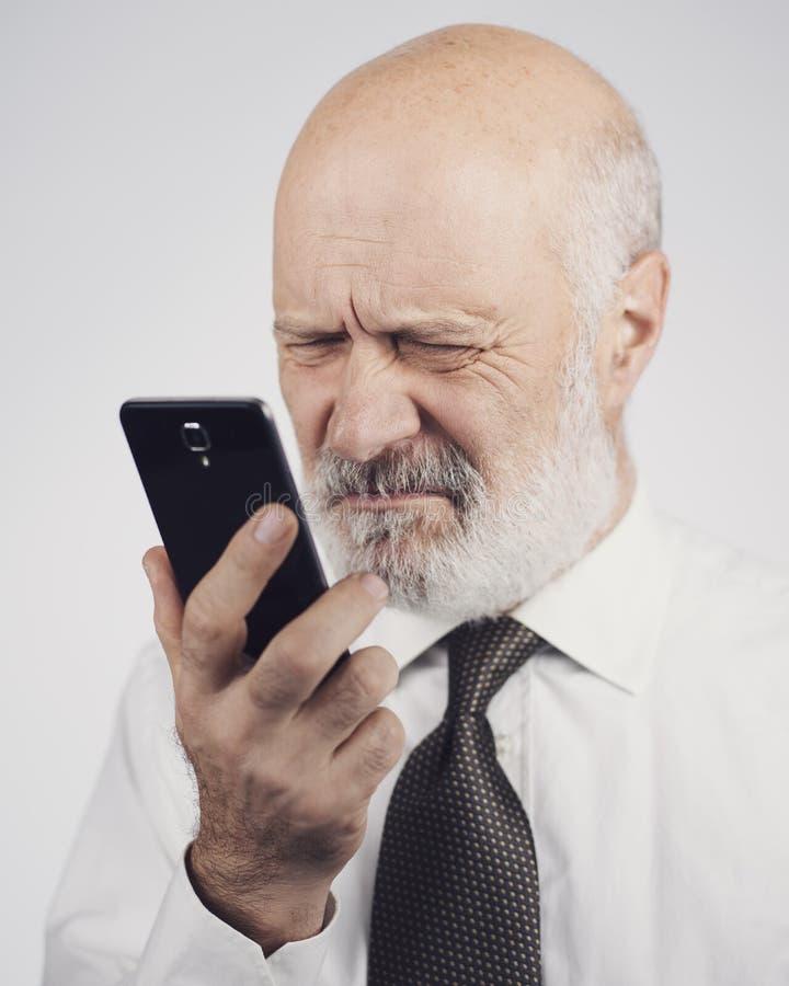 Senior man using a phone and having eyesight problems stock images