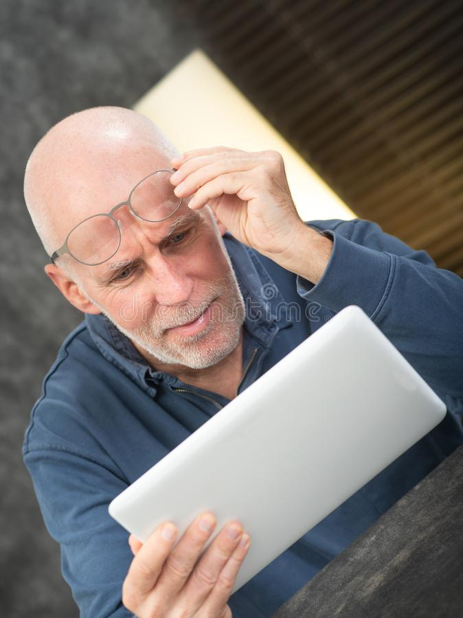 Senior man using tablet, he is having difficulties and vision problems. Senior man using a tablet, he is having difficulties and vision problems royalty free stock photos