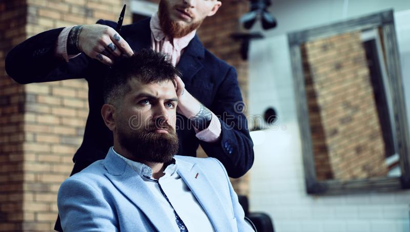 Senior man visiting hairstylist in barbershop. Brutal guy in modern Barber Shop. Hair Preparation is just for the stock photography