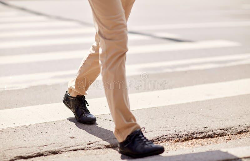 Senior man walking along city crosswalk stock images