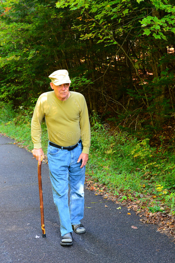Senior man walking with cane. On old highway stock photo