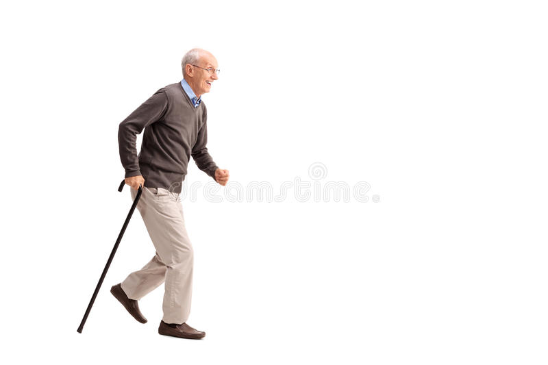 Senior man walking fast with a cane. Full length portrait of a rushing senior walking fast with a cane isolated on white background stock photography