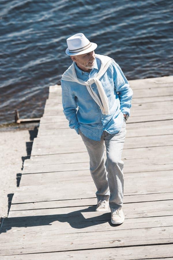Senior man walking by pavement on the riverside at daytime. Fashionable senior man walking by pavement on the riverside at daytime royalty free stock photo