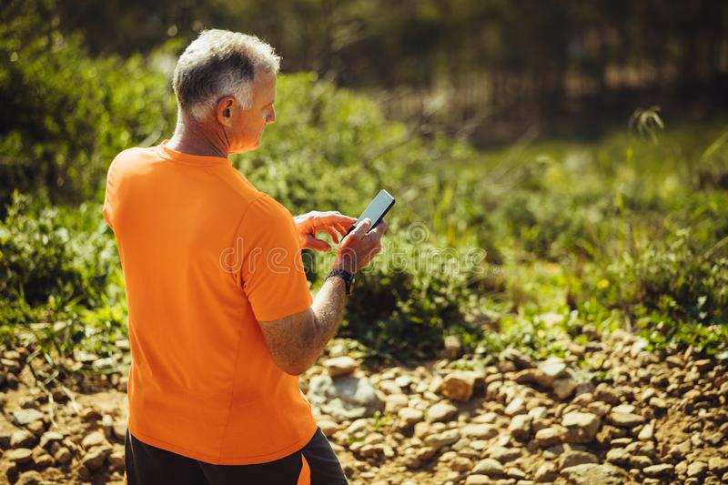 Senior man walking on a rocky path royalty free stock images