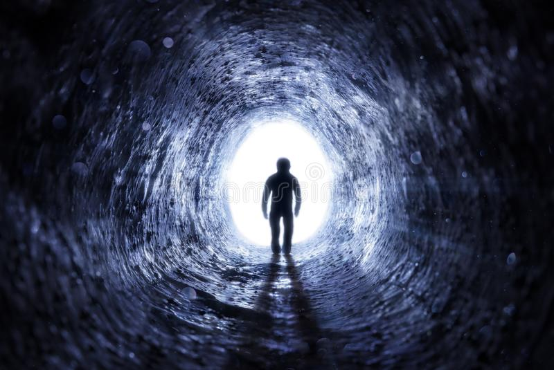 Senior Man Walking To The Light At The End Of The Tunnel royalty free stock images