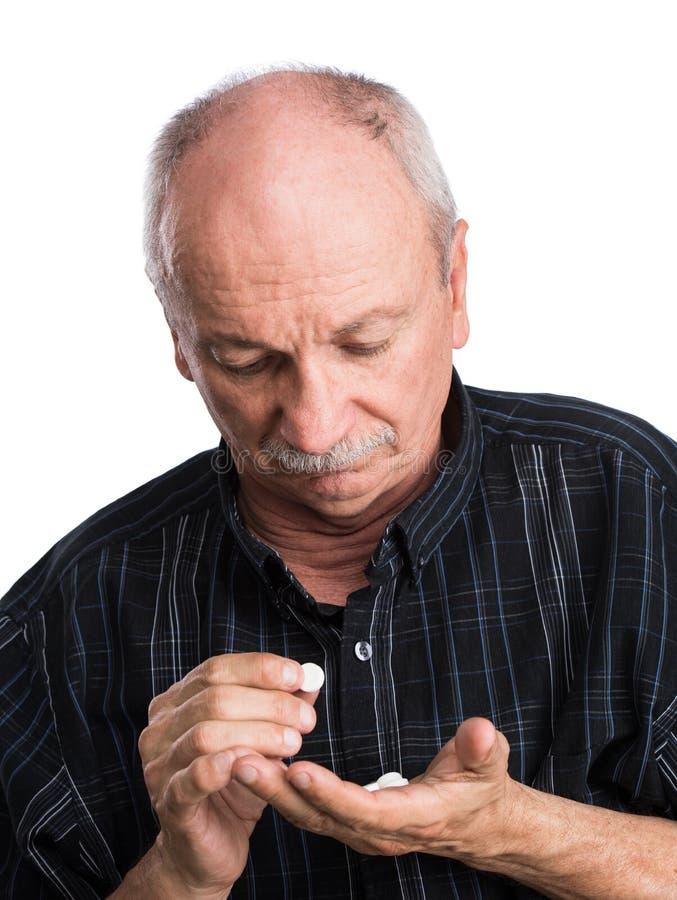 Senior man wants to take a pill stock photos