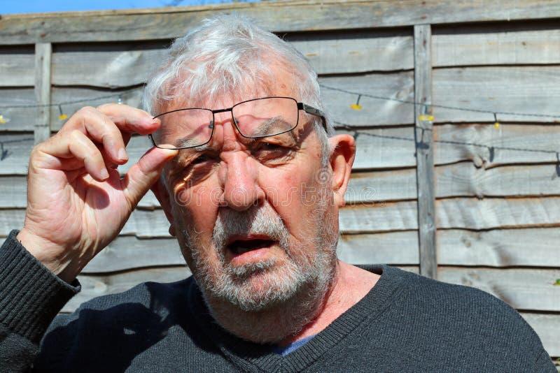 Senior man wearing spectacles glaring towards camera. A Senior man wearing eye glasses or spectacles looking towards camera and glaring. Looking annoyed lifting stock photo