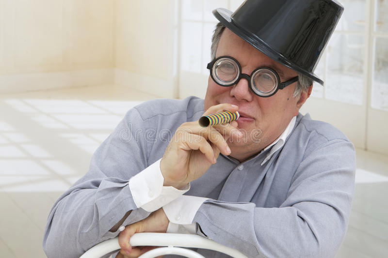 Senior man wearing party hat, and funny eyes stock images
