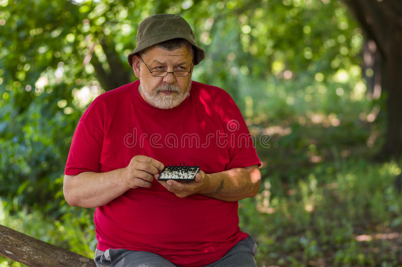 Senior man wearing red t-shirt thinks over next move while playing mini-chess royalty free stock images