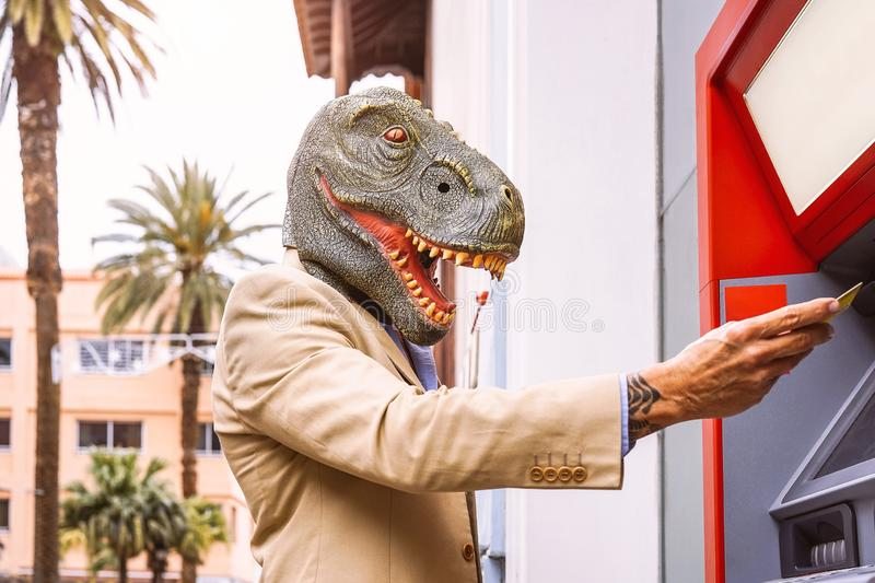 Senior man wearing t-rex dinosaur mask withdraw money from bank cash machine with debit card royalty free stock photo