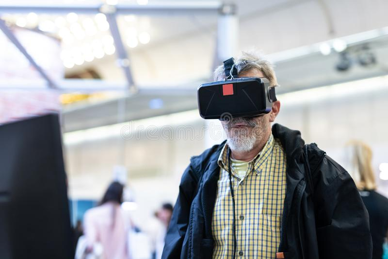 Senior man wearing virtual reality goggles watching virtual reality presentation. stock photos