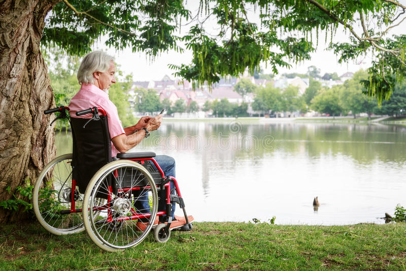Senior Man In Wheelchair. Enjoying time outdoors royalty free stock images