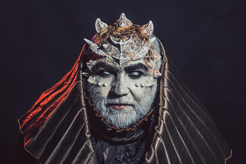 Senior man with white beard dressed like monster. Fantasy concept. Man with thorns or warts, face covered with glitters. Demon with golden hood on black stock photography