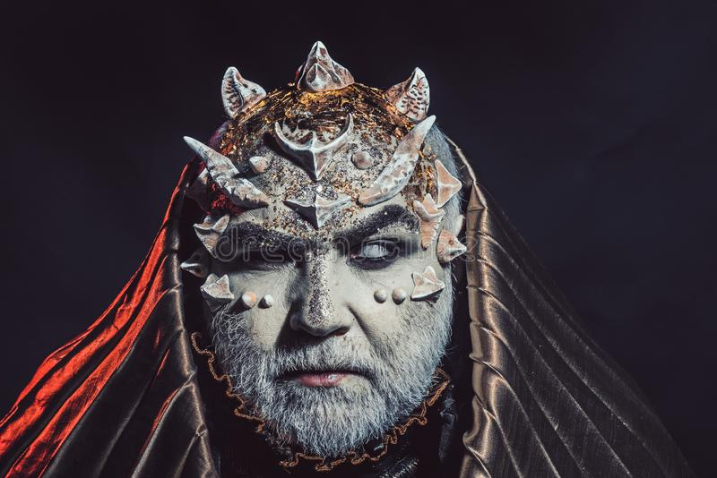 Senior man with white beard dressed like monster. Man with thorns or warts, face covered with glitters. Fantasy concept. Demon with golden hood on black stock photo