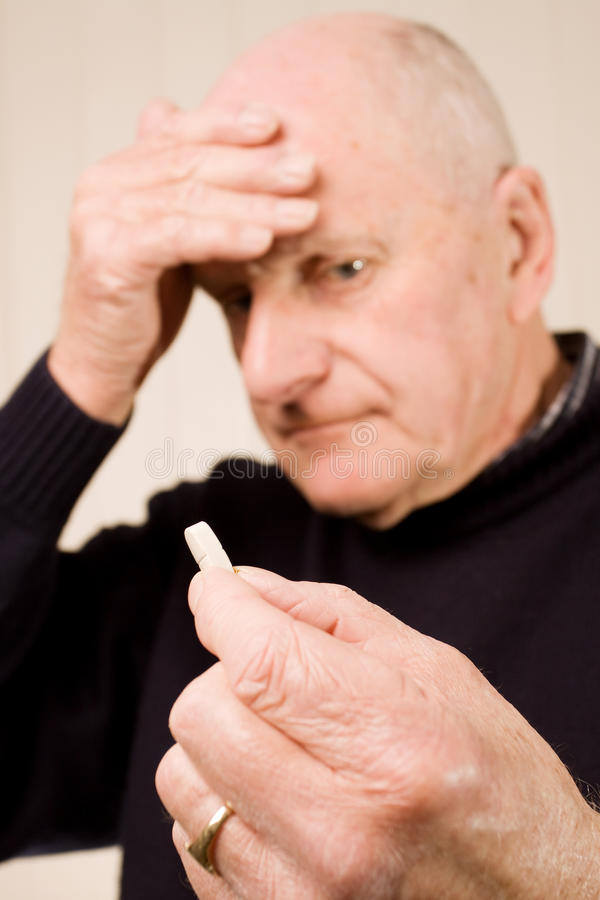 Free Senior Man With Headache Holding Tablet Or Pill Royalty Free Stock Images - 13160449