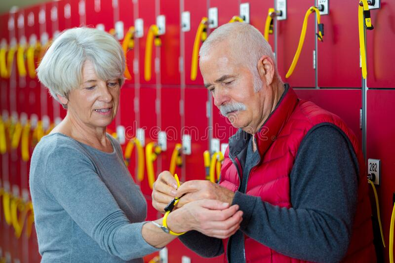 Senior man and woman chatting in locker room royalty free stock image