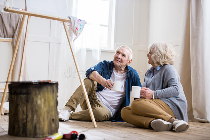 Senior man and woman drinking coffee in art workshop stock image