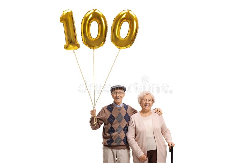 Senior man and woman with a golden number hundred balloon. Senior men and women with a golden number hundred balloon isolated on white background royalty free stock photo