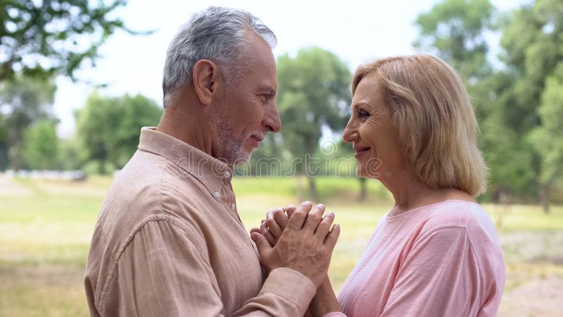 Senior man and woman holding hands, looking each other with love, happy couple royalty free stock photos