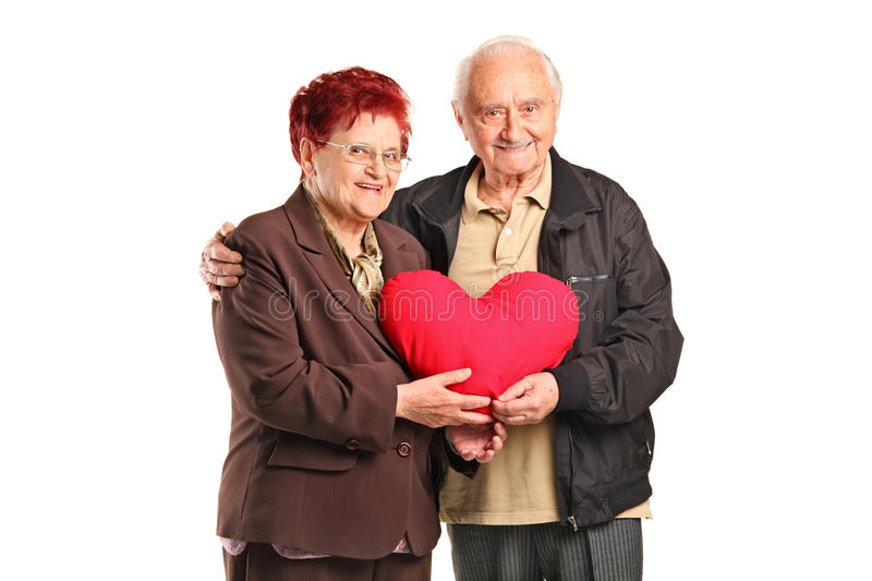 Senior man and woman holding a heart shaped pillow royalty free stock photos