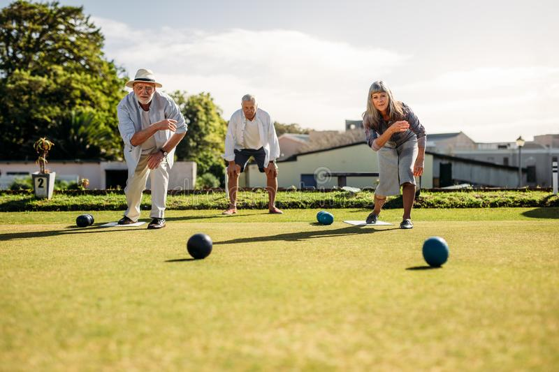 Senior man and woman playing boules in a lawn stock image