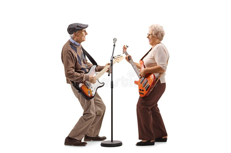 Senior man and woman playing electric guitars stock images