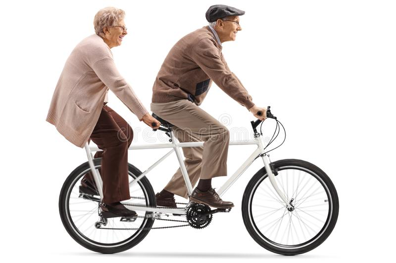 Senior man and woman riding a tandem bicycle. Full length shot of a senior man and woman riding a tandem bicycle isolated on white background royalty free stock image