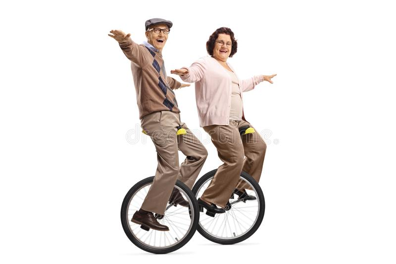 Senior man and woman riding unicycles and smiling stock images