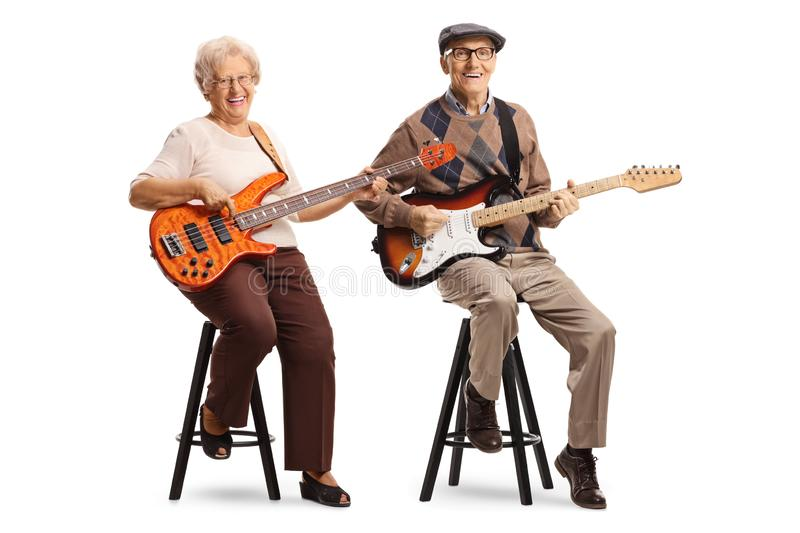 Senior man and woman sitting and playing electric guitars. Full length portrait of a senior men and women sitting and playing electric guitars isolated on white stock photo