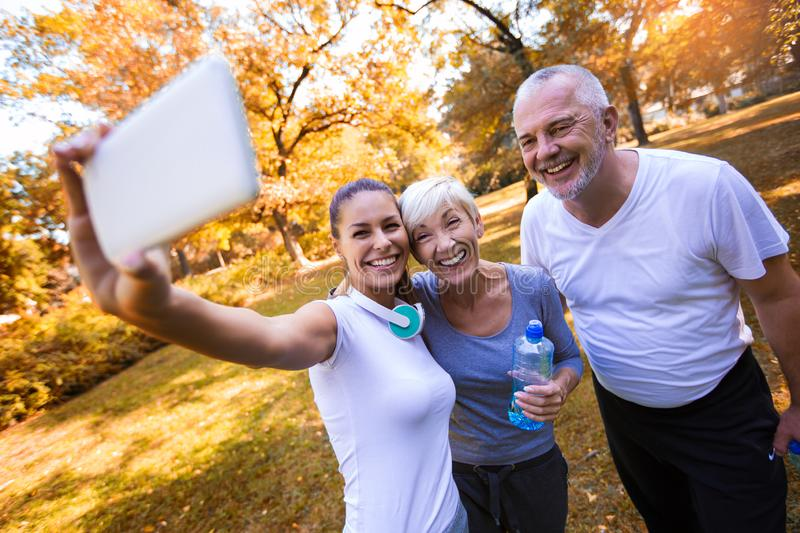 Senior man and woman and young female instructor workout on fresh air make selfie with smart phone. stock photo