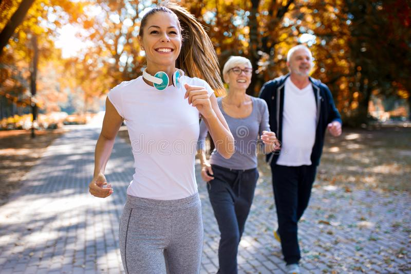 Senior man and woman and young female instructor  workout on fresh air. stock images