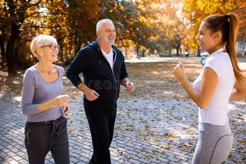 Senior man and woman and young female instructor  workout on fresh air. royalty free stock photo
