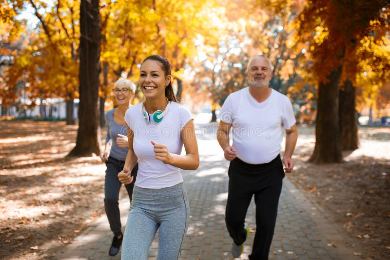 Senior man and woman and young female instructor  workout on fresh air. stock photography
