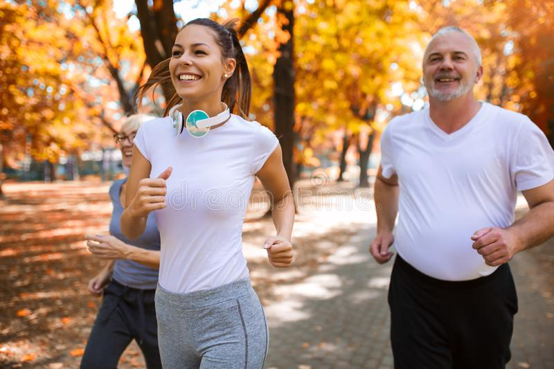 Senior man and woman and young female instructor  workout on fresh air. royalty free stock images