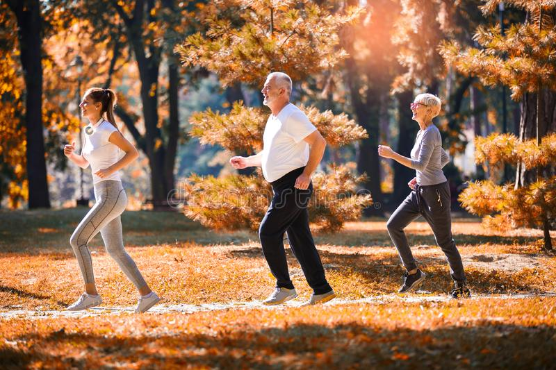 Senior man and woman and young female instructor  workout on fresh air. stock photo