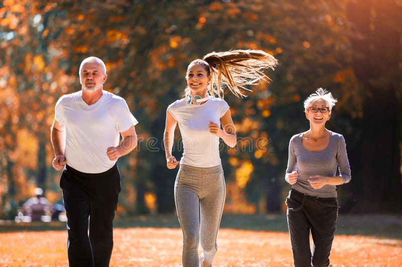 Senior man and woman and young female instructor  workout on fresh air. stock image
