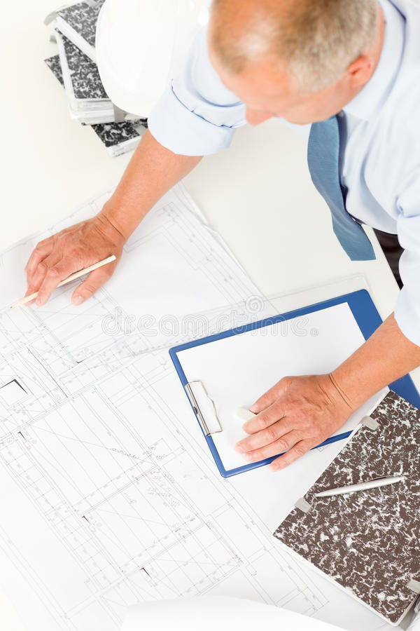 Senior man work on blueprints construction plans royalty free stock image