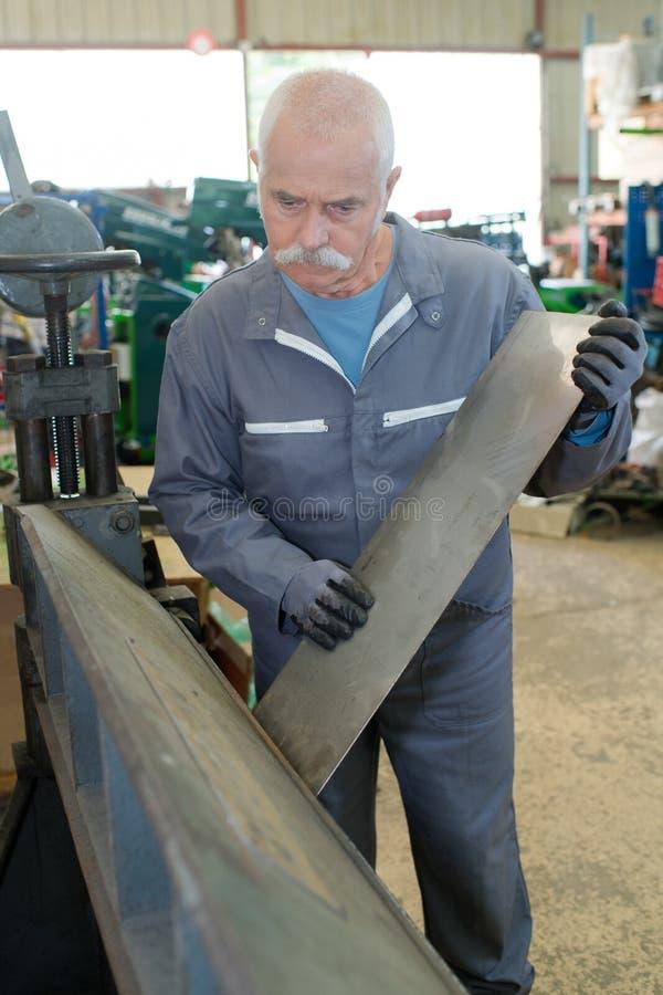 Senior man working with aluminum. Senior stock image
