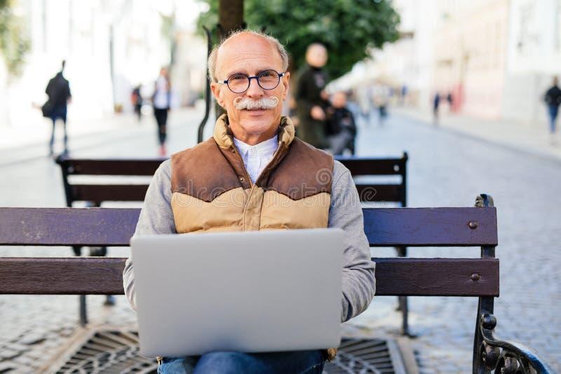 Senior man working on his laptop on the bench royalty free stock photos