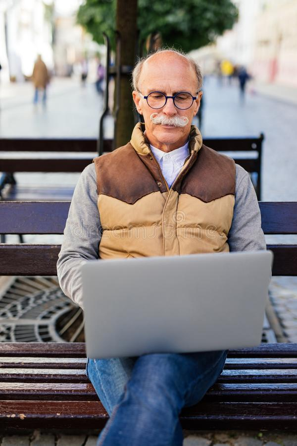 Senior man working on his laptop sitting on the bench in the city street royalty free stock photos