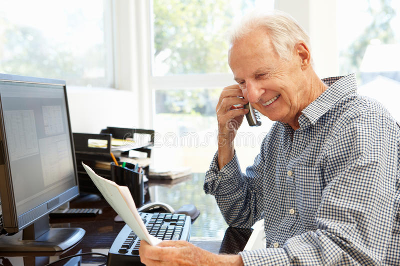 Senior man working at home stock images