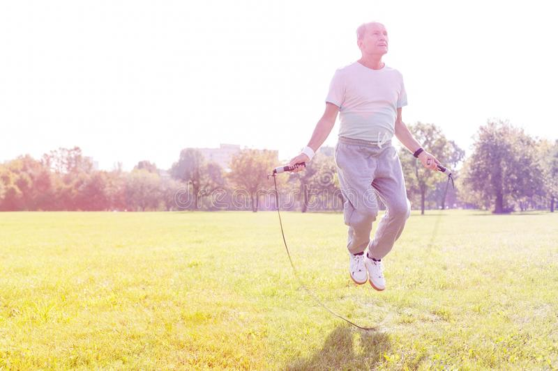 Senior man working out with skipping rope in park. Determined senior man working out with skipping rope in park stock photos
