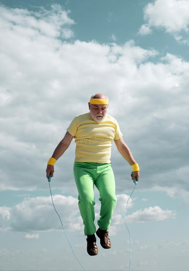 Senior man working out on a skipping rope. Senior sportsman in sport center. Healthy and sport. Senior man exercising on. Blue sky royalty free stock photos