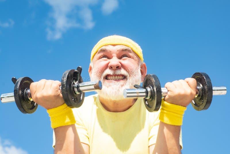 Senior man workout in rehabilitation center. Elderly man practicing sports on blue sky background. Senior fitness man stock photos