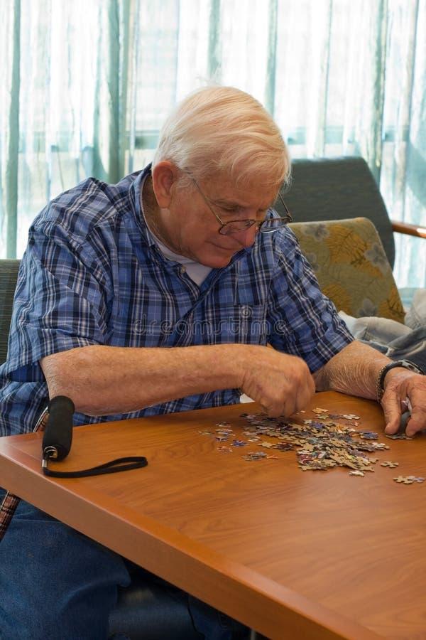 Senior man works on puzzle royalty free stock image