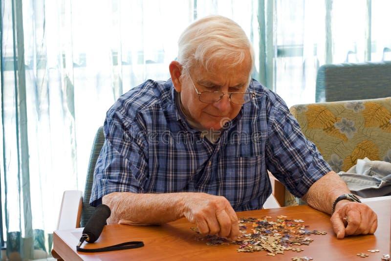 Senior man works on puzzle royalty free stock photos