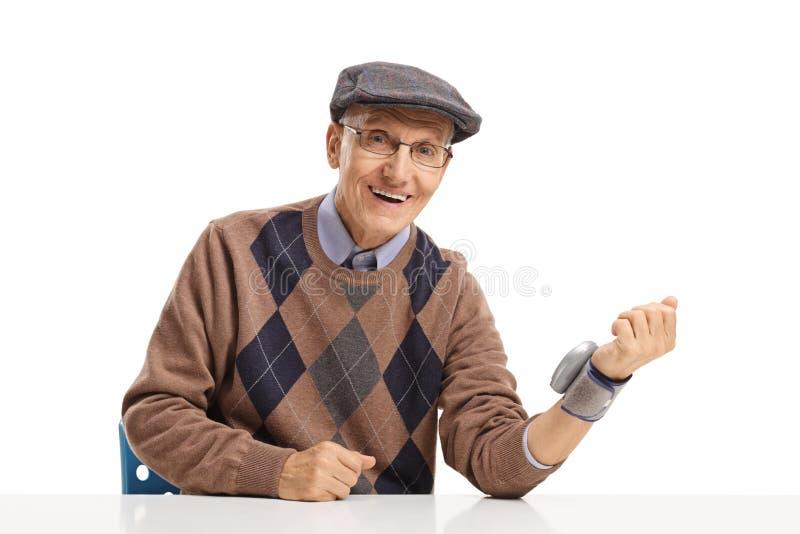 Senior man with wrist blood pressure monitor stock photos
