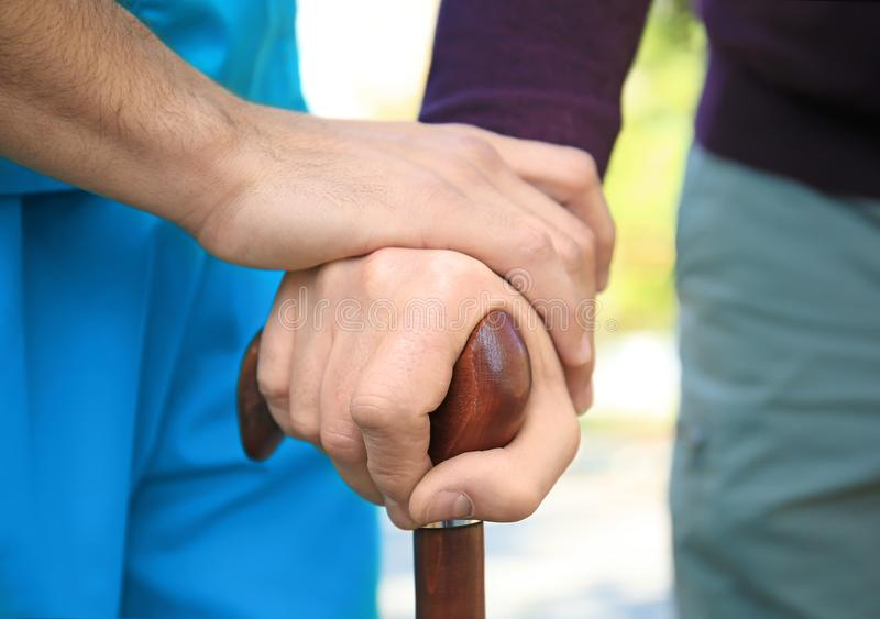Senior man and young caregiver holding hands. On walking stick, closeup stock images