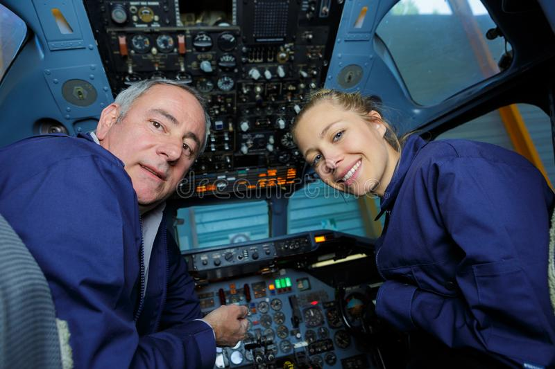 Senior man and young woman wearing overalls in aircraft cockpit. Senior men and young women wearing overalls in aircraft cockpit portrait stock photography
