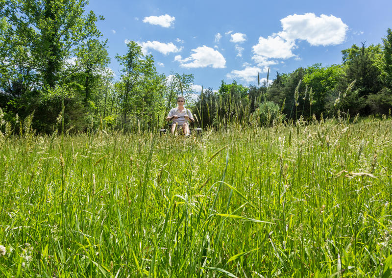 Senior man on zero turn lawnmower in meadow. Senior retired male cutting very deep grass in a meadow or field after leaving it to grow for far too long before royalty free stock photos